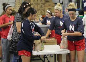 Northeast softball players volunteer at Titus County Cares every Tuesday. The team fills sacks with donated food to be distributed to schools for children of low income families in the area.