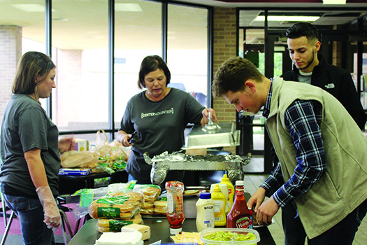 Members of Center Church prepare lunch for several of the dorm students. The church has teamed up with Jo's coffee shop to bring students food each Sunday.