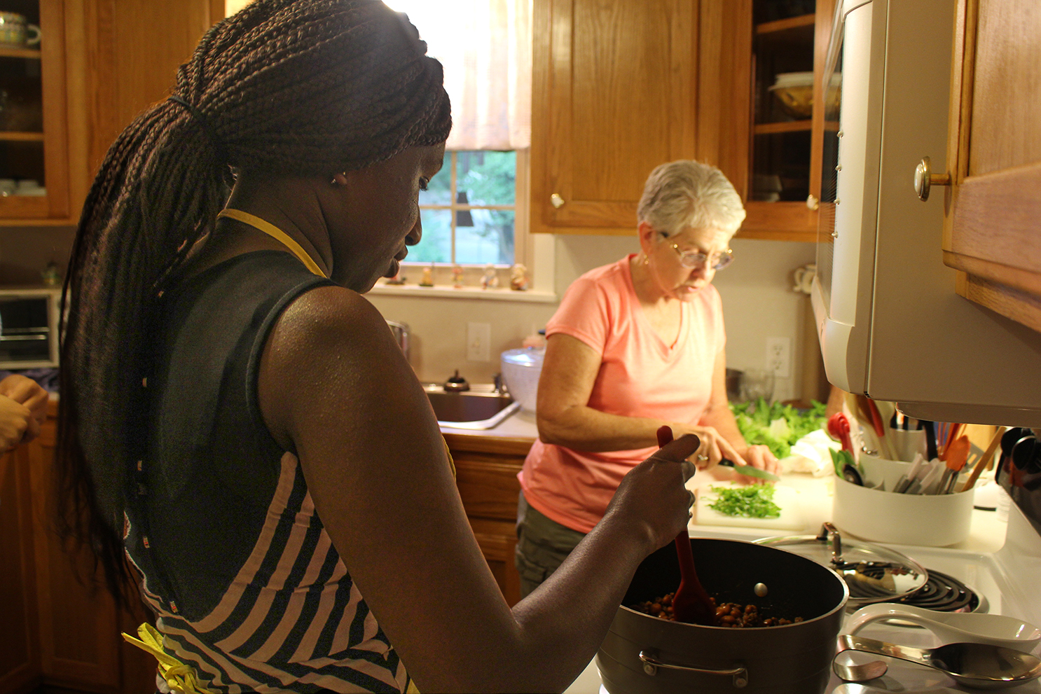 Northeast student Aji Nijie, left, and Morris prepare dinner together at Morris' house one Friday evening. The professor welcomes students into her home each weekend to share a home cooked meal and a small devotion.